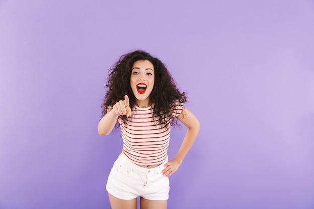 Mulher jovem feliz com cabelos cacheados no verão usar sorrindo e apontando o dedo para você