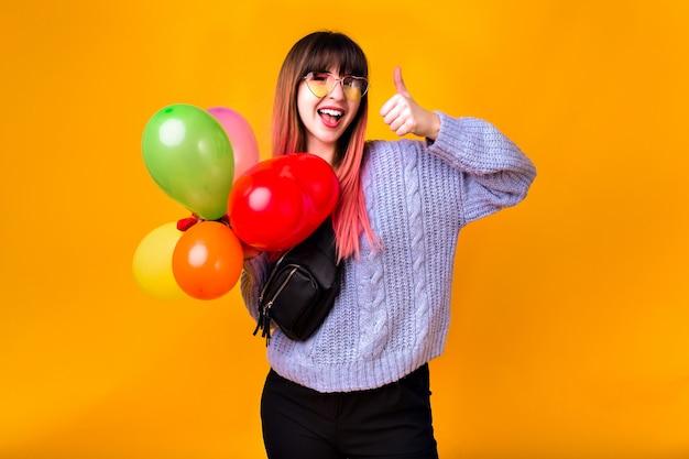 Mulher jovem feliz com cabelos rosa incomuns, se divertindo e posando na parede amarela, segurando balões coloridos de festa de aniversário, roupa da moda casual, cores em tons.