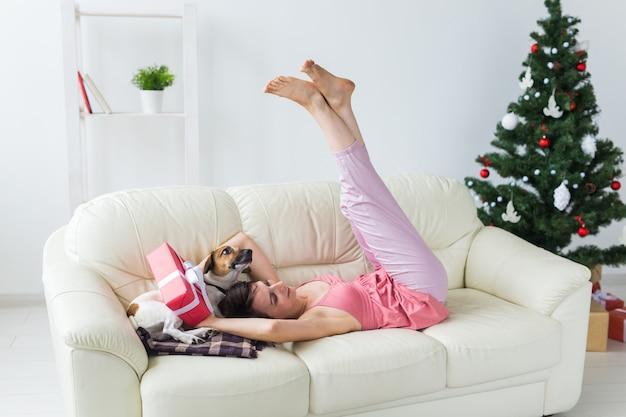 Mulher jovem feliz com cachorro adorável na sala de estar com árvore de natal.