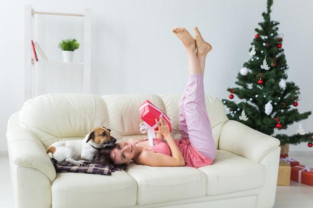 Mulher jovem feliz com cachorro adorável na sala de estar com árvore de natal