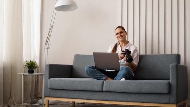 Mulher jovem feliz com câmera fotográfica usando o laptop em casa. o fotógrafo está segurando a câmera e sorrindo.