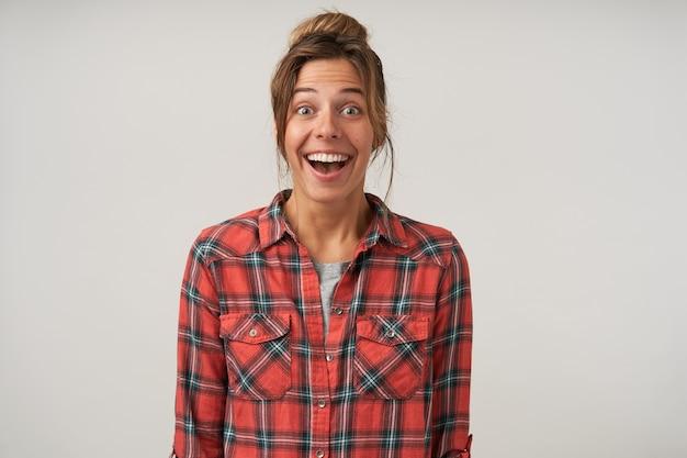 Mulher jovem feliz com camisa quadriculada em pé em um branco com as mãos para baixo, olhando alegremente com a boca aberta, penteado casual e maquiagem natural