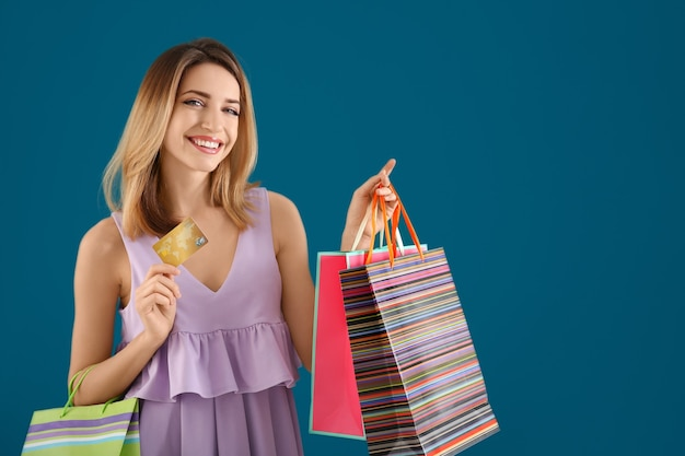 Mulher jovem feliz com cartão de crédito e sacolas de compras