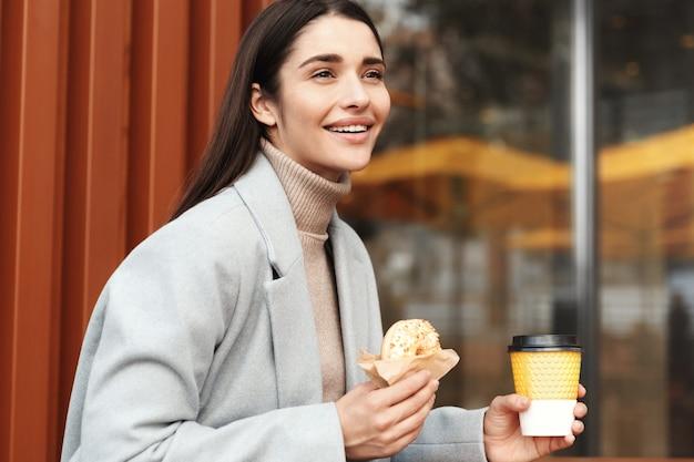 Mulher jovem feliz com casaco cinza comendo uma rosquinha em uma cafeteria.