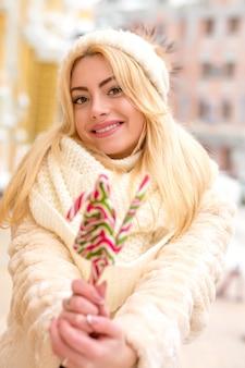 Mulher jovem feliz com chapéu e casaco quentes segurando saborosos doces de natal