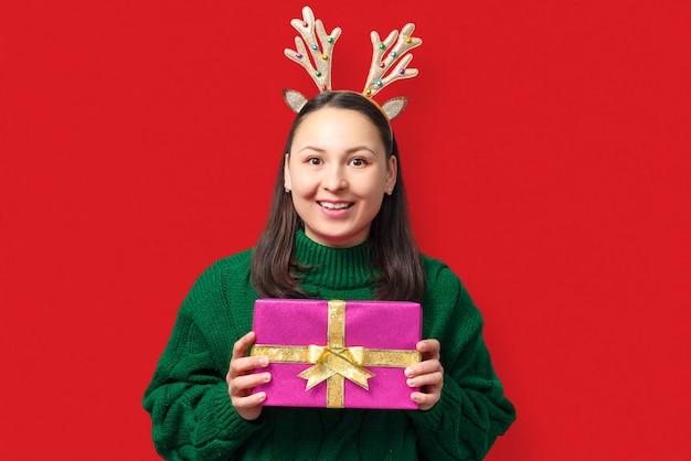 Mulher jovem feliz com chifres de veado de natal e presente em fundo vermelho
