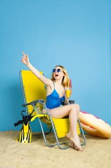 Mulher jovem feliz com coquetel, sorrindo, rindo, cumprimentando no fundo azul do estúdio. conceito de emoções humanas, expressão facial, férias de verão, fim de semana. verão, mar, oceano, álcool.