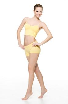 Mulher jovem feliz com corpo magro perfeito isolado na parede branca. retrato de corpo inteiro.