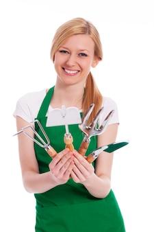 Mulher jovem feliz com equipamento de jardinagem