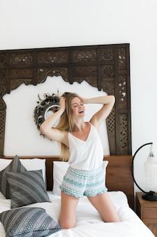 Mulher jovem feliz com fones de ouvido está ouvindo música com o telefone inteligente, dançando e sorrindo na cama