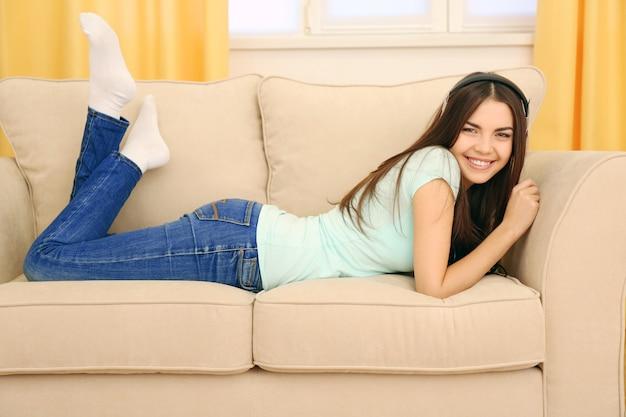 Mulher jovem feliz com fones de ouvido ouvindo música em um sofá em casa