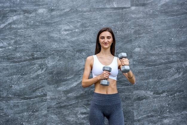 Mulher jovem feliz com halteres fazendo exercícios ao ar livre em frente a uma parede pintada moderna