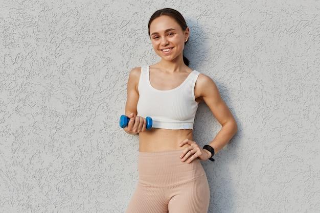 Mulher jovem feliz com halteres na mão, fazendo exercícios ao ar livre em frente à parede cinza