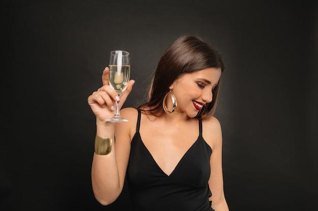 Mulher jovem feliz com joias douradas em um vestido preto bebendo champanhe