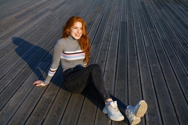 Mulher jovem feliz, com longos cabelos ruivos, de nacionalidade caucasiana, sentada com roupas casuais no parque em um deck de madeira em um dia ensolarado e sorrindo
