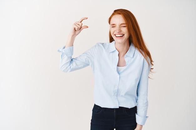 Mulher jovem feliz com longos cabelos vermelhos mostrando algo pequeno, demonstra um objeto minúsculo e rindo, em pé sobre uma parede branca