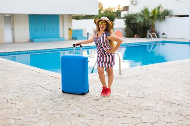 Mulher jovem feliz com mala azul chegando ao resort