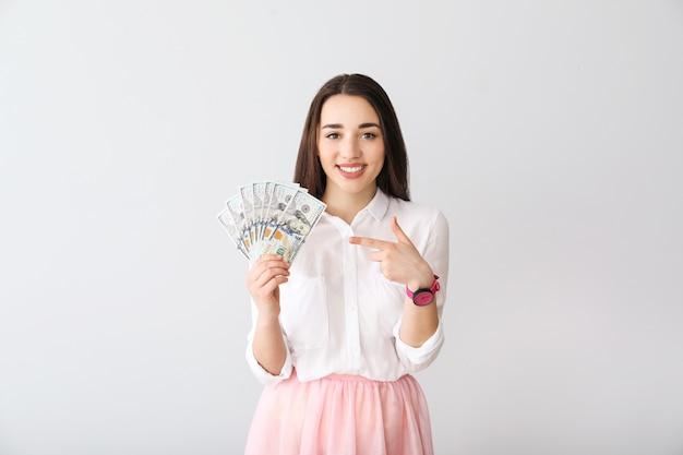 Mulher jovem feliz com notas de dólar em cinza