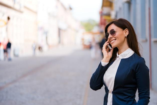 Mulher jovem feliz com óculos de sol fala por telefone na rua