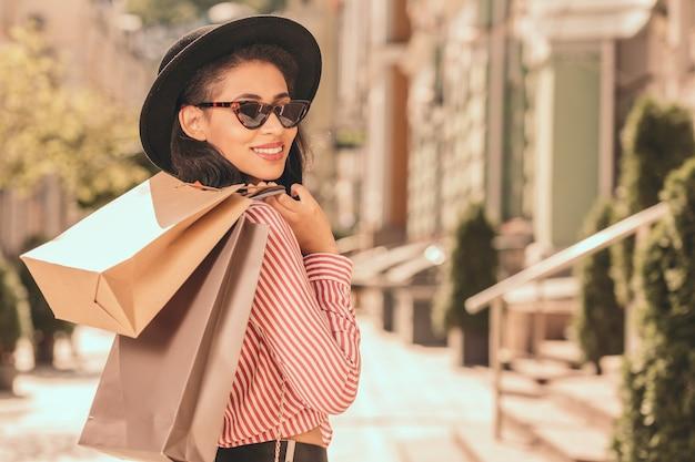 Mulher jovem feliz com óculos escuros e chapéu colocando sacolas de compras no ombro