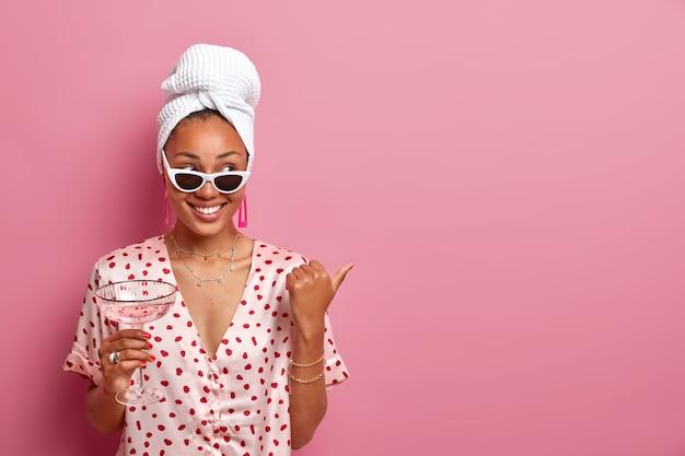 Mulher jovem feliz com pele saudável, usa roupas casuais e óculos de sol, bebe um coquetel fresco, anuncia algo e aponta no espaço da cópia,
