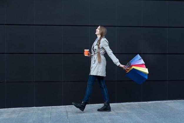 Mulher jovem feliz com sacos coloridos e copo de papel andando na rua.