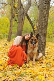 Mulher jovem feliz com seu cão pastor alemão no parque outono