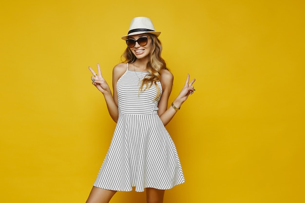 Mulher jovem feliz com sorriso encantador em vestido listrado branco, chapéu elegante e posando de óculos de sol da moda