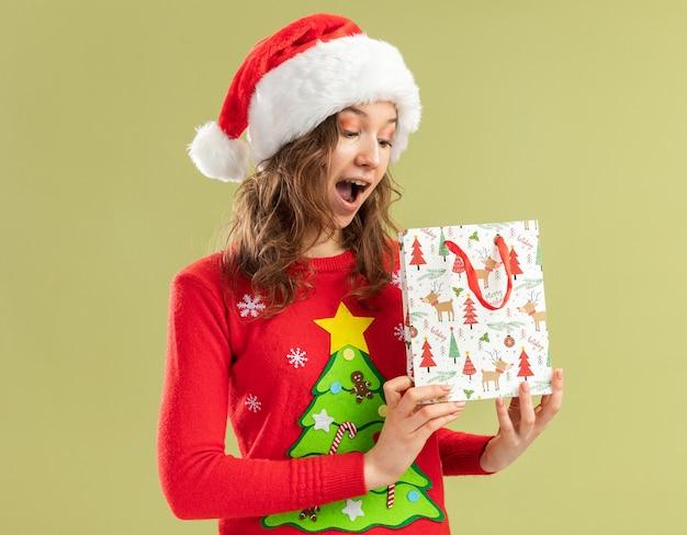 Mulher jovem feliz com suéter vermelho de natal e chapéu de papai noel segurando um saco de papel com um presente de natal sorrindo alegremente em pé sobre a parede verde
