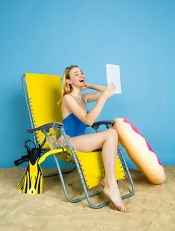 Mulher jovem feliz com tablet leva selfie ou vlog sobre como viajar no fundo azul do estúdio. conceito de emoções humanas, expressão facial, férias de verão, fim de semana. verão, mar, oceano, álcool.