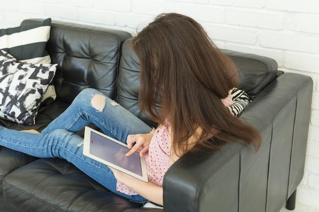 Mulher jovem feliz com tablet pc deitada no sofá
