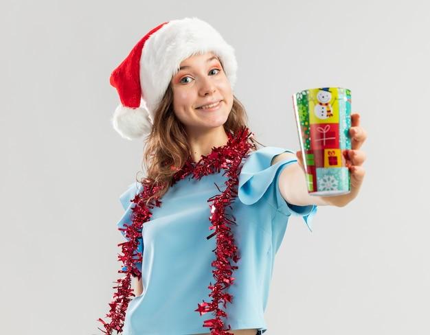 Mulher jovem feliz com top azul e chapéu de papai noel com enfeites em volta do pescoço mostrando copo de papel colorido sorrindo alegremente