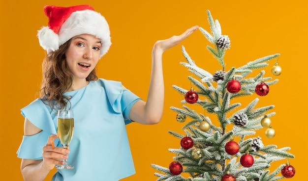 Mulher jovem feliz com top azul e chapéu de papai noel segurando uma taça de champanhe, apresentando a árvore de natal com o braço da mão em pé sobre a parede laranja
