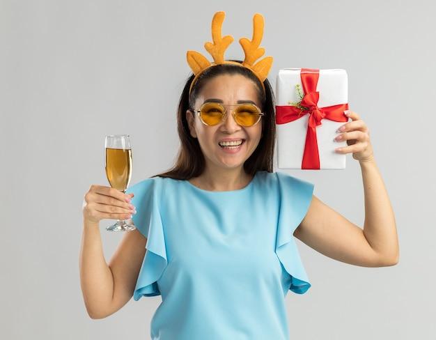 Mulher jovem feliz com top azul, vestindo uma borda engraçada com chifres de veado e óculos amarelos segurando uma taça de champanhe e um presente de natal sorrindo alegremente