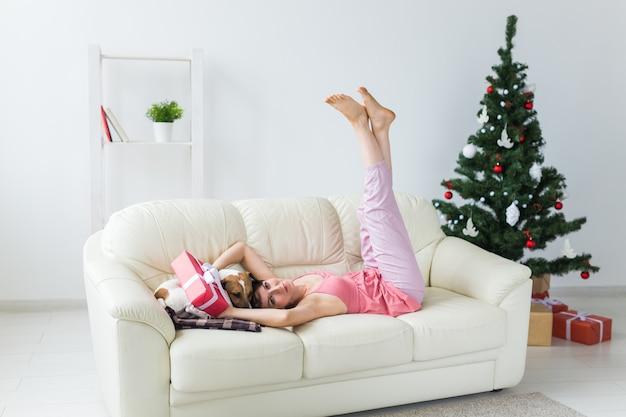 Mulher jovem feliz com um cachorro adorável na sala de estar com a árvore de natal. conceito de férias.