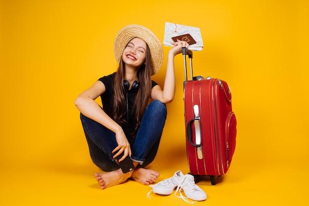 Mulher jovem feliz com um chapéu vai de férias, em uma viagem, tem bilhetes de avião e uma grande mala vermelha