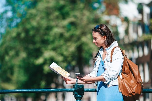 Mulher jovem feliz com um mapa da cidade de bicicleta em uma cidade europeia