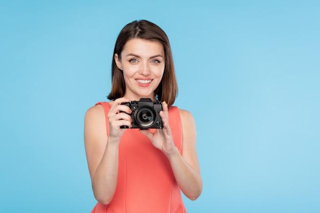 Mulher jovem feliz com um sorriso cheio de dentes segurando uma câmera na frente dela enquanto vai tirar uma foto sua