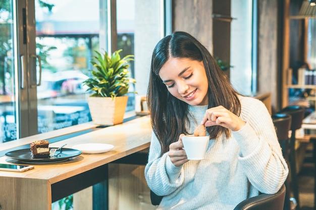 Mulher jovem feliz com um suéter quente com uma xícara de café e um biscoito sentado perto de uma janela