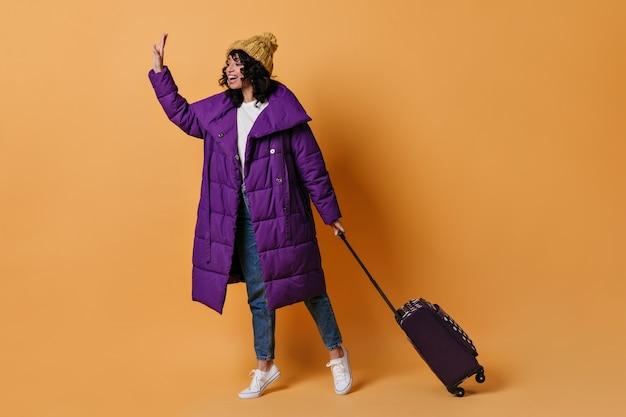 Mulher jovem feliz com uma mala acenando com a mão