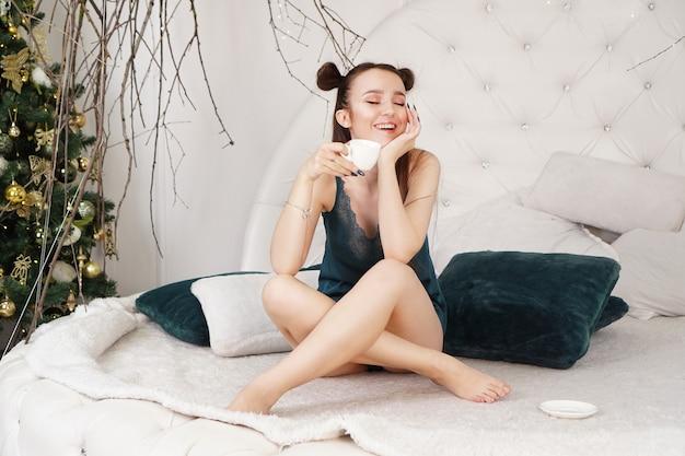 Mulher jovem feliz com uma xícara de café ou chá na cama no quarto de casa, hora da manhã de natal