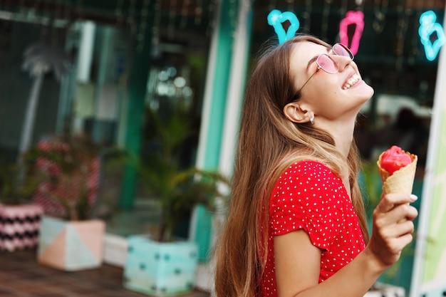 Mulher jovem feliz com vestido de verão e óculos escuros, tomando sorvete doce em um dia ensolarado ao ar livre, rindo despreocupada e aproveitando as férias de verão