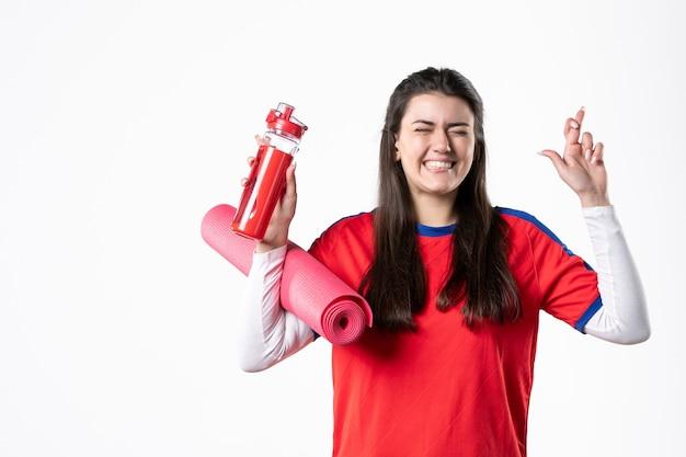 Mulher jovem feliz com vista frontal em roupas esportivas e tapete de ioga