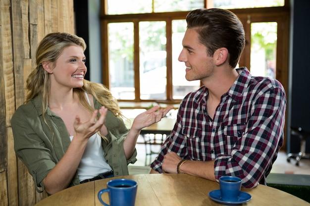 Mulher jovem feliz conversando com um homem à mesa de um café