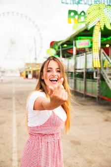 Mulher jovem feliz, convidando alguém com uma mão no parque de diversões