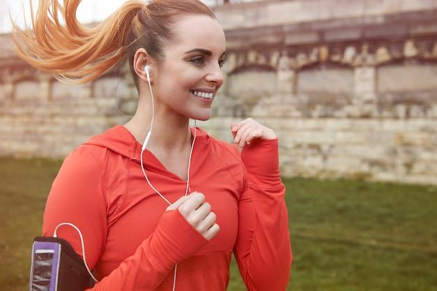 Mulher jovem feliz correndo ao ar livre. correr é ótimo cardio matinal