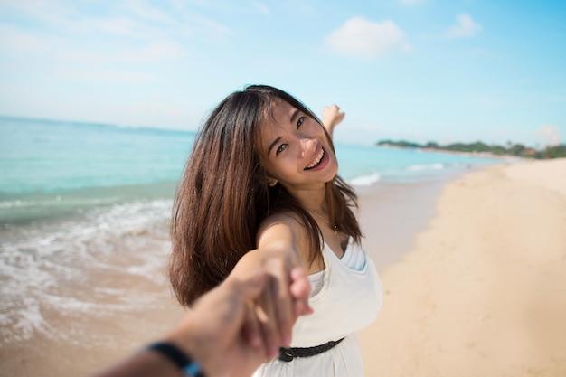Mulher jovem feliz correndo na praia