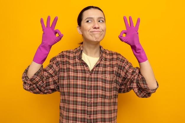 Mulher jovem feliz da limpeza com roupas casuais e luvas de borracha, sorrindo alegremente, mostrando a placa de ok em pé sobre a parede laranja