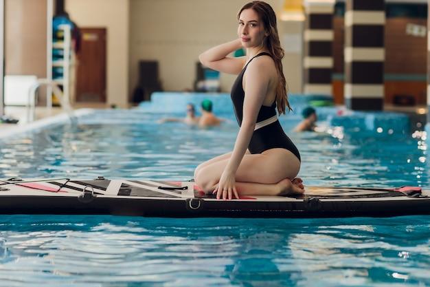 Mulher jovem feliz de biquíni tomando banho de sol em uma prancha de surf no instrutor de piscina em uma academia de surfe coberta.