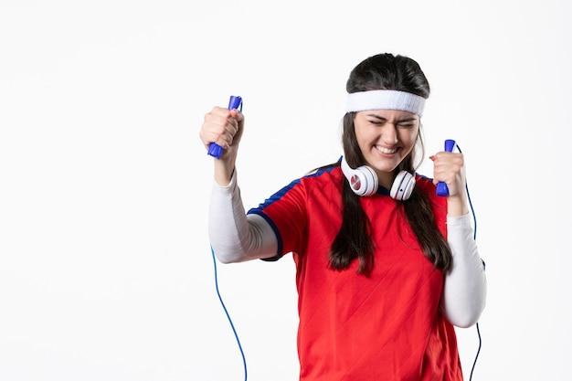 Mulher jovem feliz de frente com roupas esporte e cordas de pular